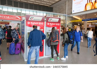 VENICE, ITALY-SEPTEMBER 26, 2017: Travellers buy their train tickets at self serve kiosks located at the train station Venezia Santa Lucia, which is the central station of Venice in Italy.