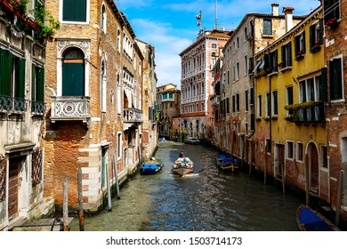 Venice on a beautiful day with small narrow canals and boats and gondolas floating under bridges. Venice, Italy, April 28, 2016.