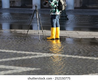 venice photographer with yellow boots at high tide in St. Mark's square
