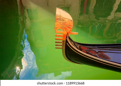 Venice: reflections, lights and colors. Particular of the iron prow-head of the gondola. The ornaments on the front  of the Gondola represent symbols of Venice.