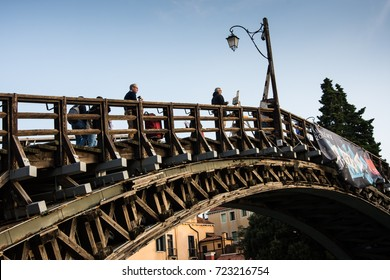 Venice - September 13, 2017: An unknown artist paints the early morning scene from Ponte Dell'Accademia as tourists pass by in Venice on September 13, 2017.