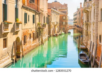 Venice street with canal, boats and gondolas