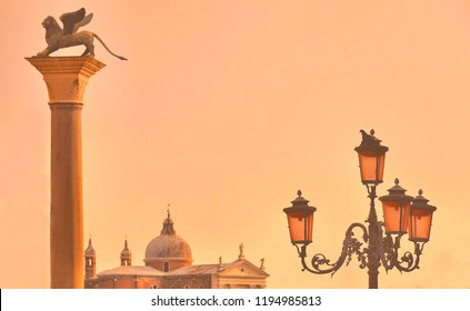 Venice sunset, famous column with winged lion, street lamp and San Giorgio Maggiore church at dusk in Venice, Italy, warm toned