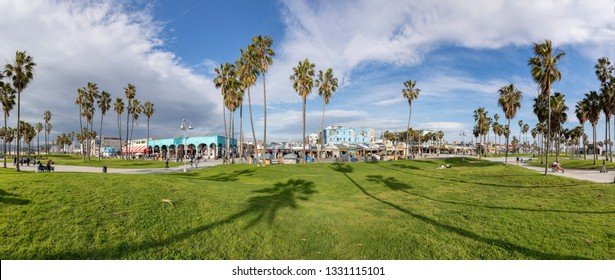 VENICE, USA - MAR 5, 2019: people enjoy scenic beach promenade with palms and colorful houses at Venice Beach in California.