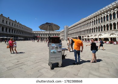 Venice, Venetia / Italy - July 17th 2020: photographers booth with parasol in the middle of Marcus Square with only few people at end of corona pandemic