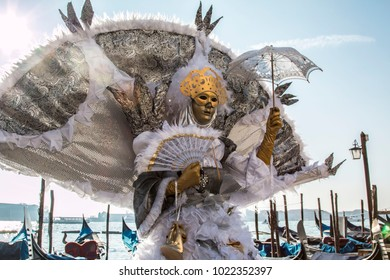 Venice, Veneto / Italy- February 4 2018: Venetian costumed model with gondolas in background