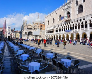 Venice, Veneto / Italy - March 2018: Tables sit mostly empty while tourists mill around St Mark's Square near Doge's Palace.
