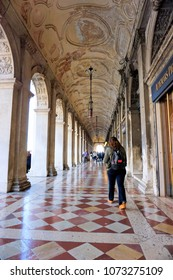 Venice, Veneto / Italy - March 2018: Tourists walk along tall stone archways inside the Doge's Palace at St Mark's Square in Venice Italy.
