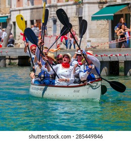 Venice, Veneto, Italy - May 24, 2015: Oarsmen welcome viewers in the Venice Vogalonga regatta. More than 1,500 boats take part in the annual historic regatta. Selective focus on the foreground