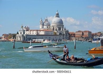 Venice, Veneto, Italy - September 6, 2016: Gondolieri with tourists on the waterfront Riva degli Schiavoni in front of the Basilica of Santa Maria della Salute of Venice in Italy.