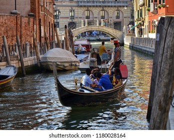 Venice, Veneto region, August 2018 Italy. Typical view of one of the small secondary canals of Venice. Tourists on board the gondola will enjoy the atmosphere of the place.