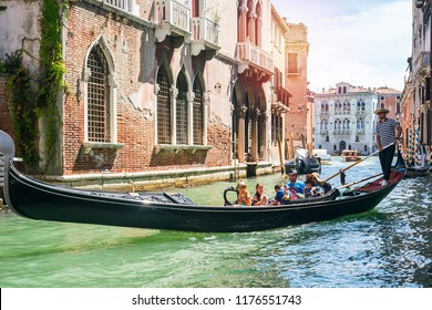 Venice (Venezia), Italy, August 14, 2018: Gondolier ride a gondola on the canal in Venice a group of people, a family.