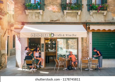 Venice (Venezia), Italy, August 14, 2018: People rest in a street cafe and wine bar.