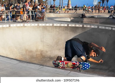 VENICE-AUG 4: A skateboarder skates sideways along the edge of a bowl while a crowd watches him at the Venice Skatepark in Venice, CA on Aug. 4, 2012.