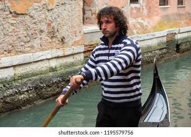 Venice/Italy - 04/16/2018: Portrait of a gondolier dressed in traditional costume controlling the gondola. Close-up.