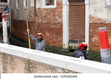 Venice/Italy - 04/16/2018: Portrait of a gondoliers dressed in traditional hats on the canal.