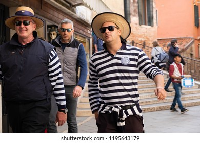 Venice/Italy - 04/18/2018: The fashionable Italian gondoliers in traditional costumes on the street in Venice.