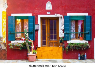 Venice/Italy - 10 27 2018: Cute ancient red facade of the residential building with old wooden shutters on the windows, vintage entrance door, flowers and cacti on the window sills. Virgin Mary above.