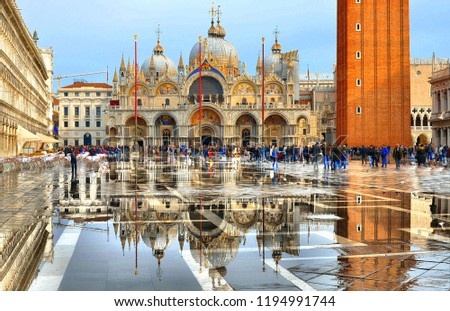 VENICE,ITALY 10.11.2016 St Mark's Square full of tourists during a flood with beautiful water reflections  of St. Marks Cathedral Basilica on wet floor.