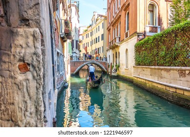 Venice/Italy - August 22, 2018: A venetian gondolier is ruling the gondola with passengers to the bridge over a channal