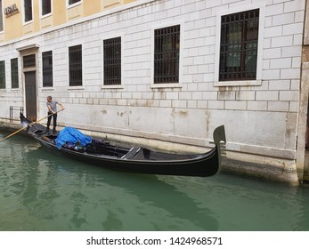 Venice/Italy. May 10, 2018. Gondolier in black and white striped shirt pushes an empty black gondola through a canal in Venice, with a white brick building in the background.