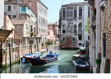 Venice/Italy - May 8, 2015: One big motorboat is moving in a canal street of Venice with motorboats anchored at walls of old houses in a sunny spring day.