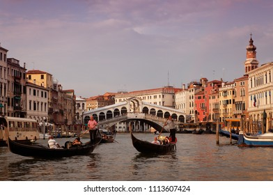 Venice,Italy,July 29th 2011: Gondoliers sailing on Grand Canal in front of the Rialto Bridge in Venice.