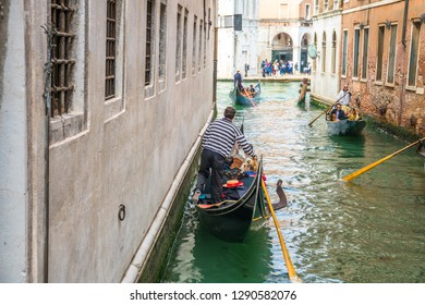 Venice,Italy-May 5,2018: Unidentified man rows gondola on May 5th, 2018 in Venice, Italy. Venice is situated across a group of 117 small islands that are separated by canals and linked by bridges