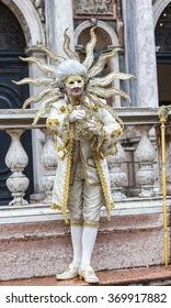 VENICE-MAR 02: Disguised man in a sun costume doing a pantomime performance in San Marco Square  on March 02,2014 in Venice, Italy, during the Carnival days.