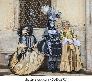 VENICE-MAR 02:Three unidentified persons wearing beautiful Venetian costumes poses near the walls of The Doge's Palace in San Marco Square on March 02,2014 in Venice, Italy, during the Carnival days.
