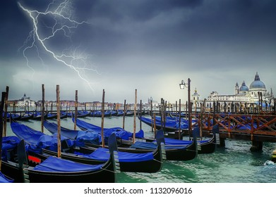 Venice's lagoon at the entrance to the Grand Canal with gondolas and the Basilica of Santa Maria della Salute during rain and thunderstorm, Italy