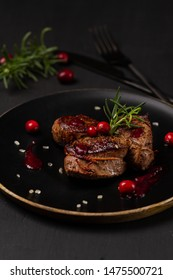 Venison or deer steak with ingredients like sea salt, rosemary and cranberry on black plate. Food background for restaurant.