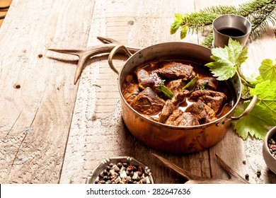 Venison Goulash Stew in Copper Pot with Bowls of Seasoning on Wooden Surface with Copy Space Surrounded by Deer Antlers and Leaves