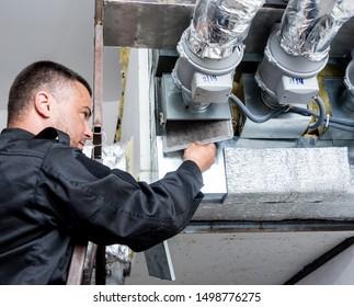 Lüftungsreinigung. Spezialist bei der Arbeit. Reparatur-Lüftungssystem (HVAC).  Industrieller Hintergrund