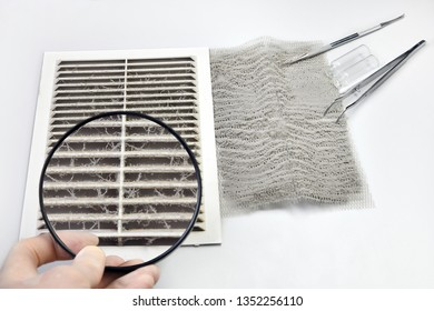 Ventilation grill is covered with dust. Inspecting dust under a magnifying glass.