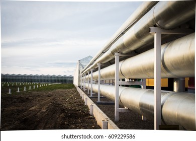 Ventilation pipes inside industrial facility, factory . A beautiful metal tube with the reflection of the sunset. The pipes go to the horizon. Background with perspective