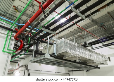 Ventilation system and pipe systems installed on industrial building ceiling.