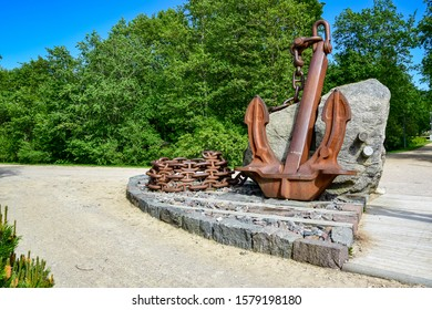 Ventspils, Latvia - 11/06/2017: Memo, large rusty anchor monument, chain, green trees.