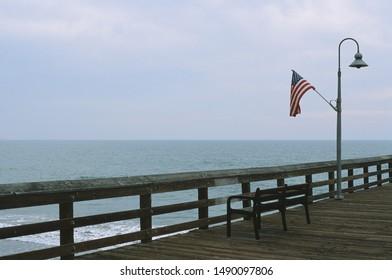 Ventura, California - November 10 2018: An empty bench and American flag at the Ventura pier.