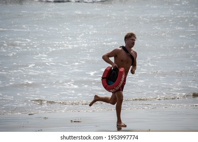 Ventura, California, USA -  June 19, 2020: A lifeguard at Ventura Harbor runs along  the shore with his rescue equipment, including floatation device and fins.