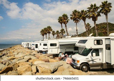 VENTURA COUNTY, CALIFORNIA, UNITED STATES - OCTOBER 06, 2006. Two probably retired men enjoy a beautiful sunny day surrounded by several RVs on the rocky beaches of Faria Beach National Park.
