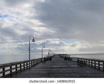 Ventura pier after the storm, wet with soft light and dramatic clouds.