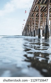 Ventura pier during early summer. great for fishing, suntanning, eating tacos, and walking along the wooden deck. water aqua clear. california beaches and clear skies with clouds