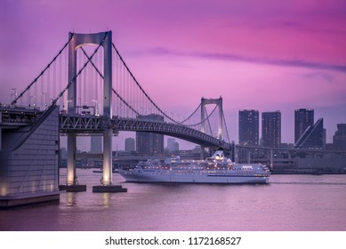 Venus cruise ship sailing in Odaiba Bay under the Rainbow Bridge in a pink sunset light.