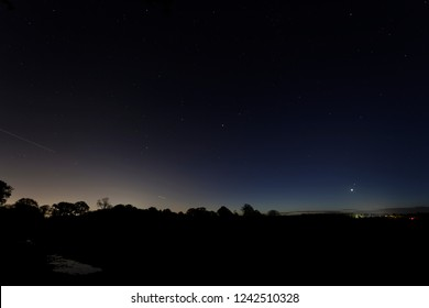 Venus rises just above the horizon with the star Spica just above from the constellation virgo a distant farm is lit up and trees silhouette against the bright dawn sky Oakley Hampshire
