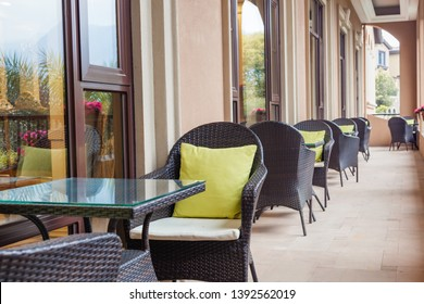 The veranda,street view of a outdoor coffee terrace with tables and wickerchairs by the window.