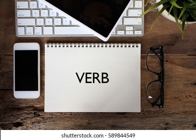 VERB Concept. Words on notebook with smartphone, keyboard and tablet on wooden table