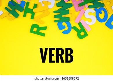 VERB text with ABC wooden letters alphabet scattered on a yellow background. Education and copy space