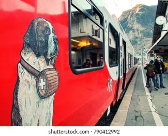 VERBIER, SWITZERLAND - FEBRUARY 07, 2011.  Ski resort in Swiss Alps. Saint-Bernard express train at railway station. Image of Saint-Bernard rescue dog at a coach.