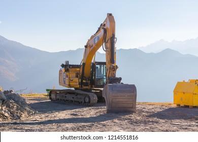 Verbier/Switzerland- 09.09.18 : Classic Yellow Cat bulldozer Backhoe mountain sun